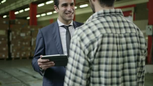 Businessman and supervisor in shipping facility talking to young man at work