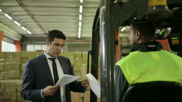 Businessman in shipping facility speaking with manual worker operating forklift