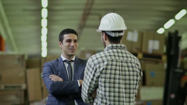 podnikatel a supervizor v přepravní zařízení, mluvit s mladým mužem