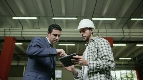 podnikatel a supervizor v přepravní zařízení, mluvit s mladým mužem v práci