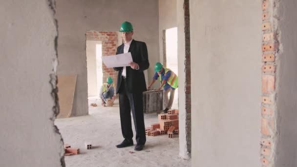 inženýr s plány v novém domě