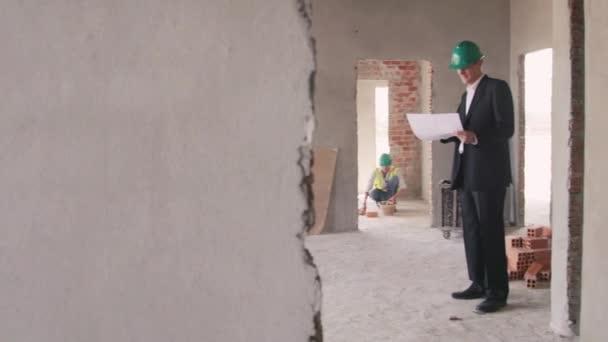 konstruktér a architekt s plány v novém domě