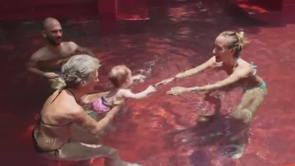Little girl swim with teacher and parents