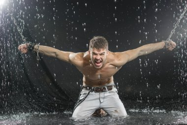 Strong man in chains posing under the rain, aqua studio