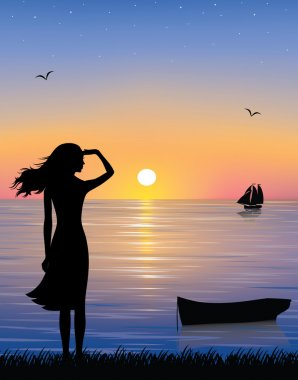 Silhouette of a boat and a graceful woman watching a ship at the sea with a beautiful sunset.