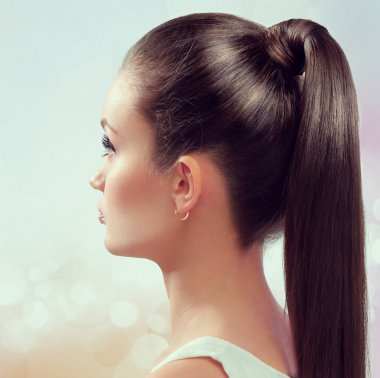 Young female with healthy shining brown hairs put in pony tail.