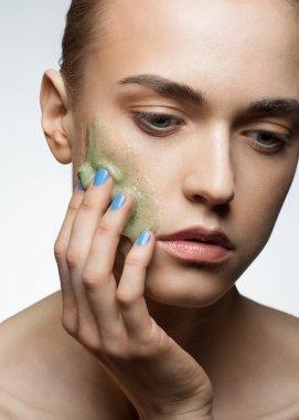 Woman applying facial scrub