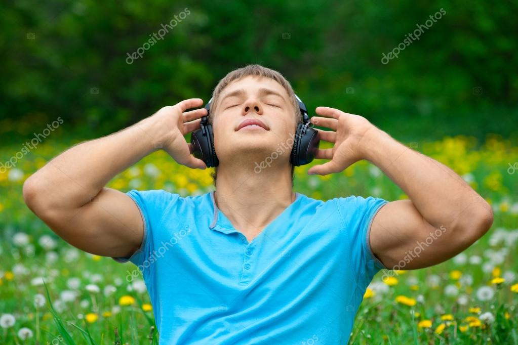 Portrait of a young man listening to music outdoors