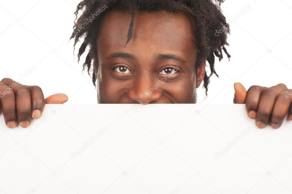 Cheerful young african american man with blank billboard peeking, isolated on white background