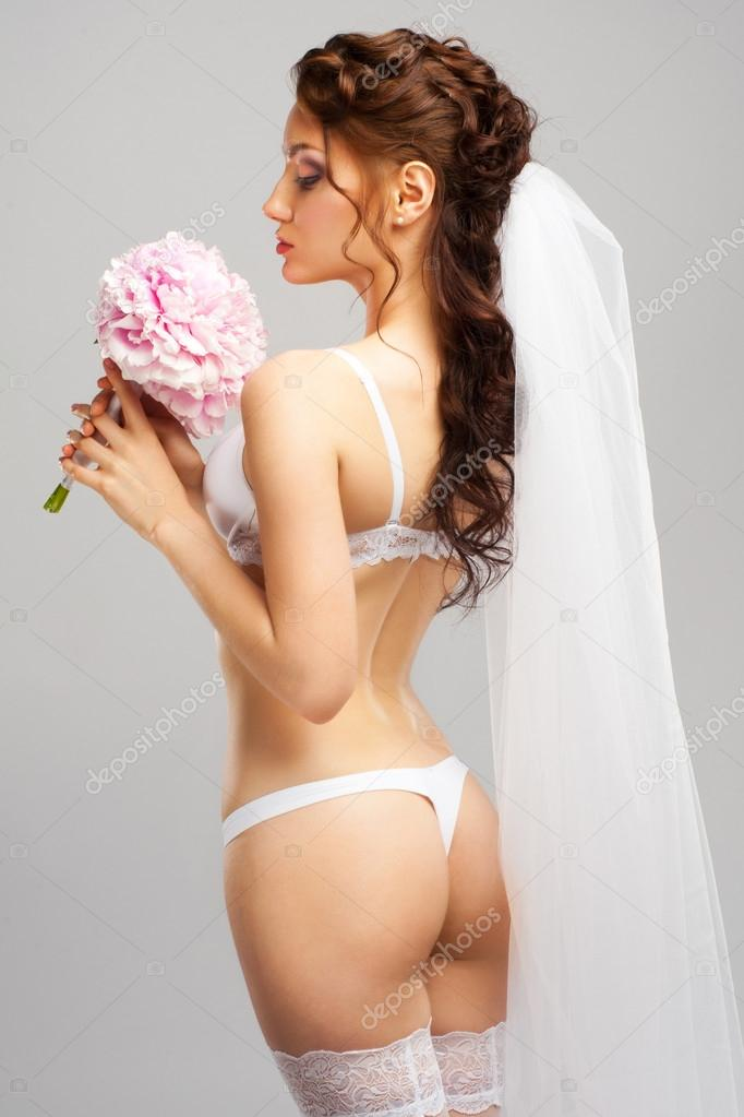 78517a282a9 Portrait of a sensual bride wearing white lingerie and white veil with  bouquet of peonies — Photo by malyuginphoto