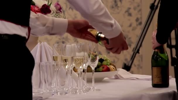 Waiter in the party is pouring a sparkling champagne on the champagne glasses