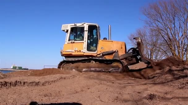 A heavy bulldozer moving some soil on the ground