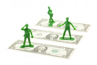 Military toy soldier standing over the dollar bill