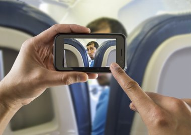 Photographing a surprised man on a plane