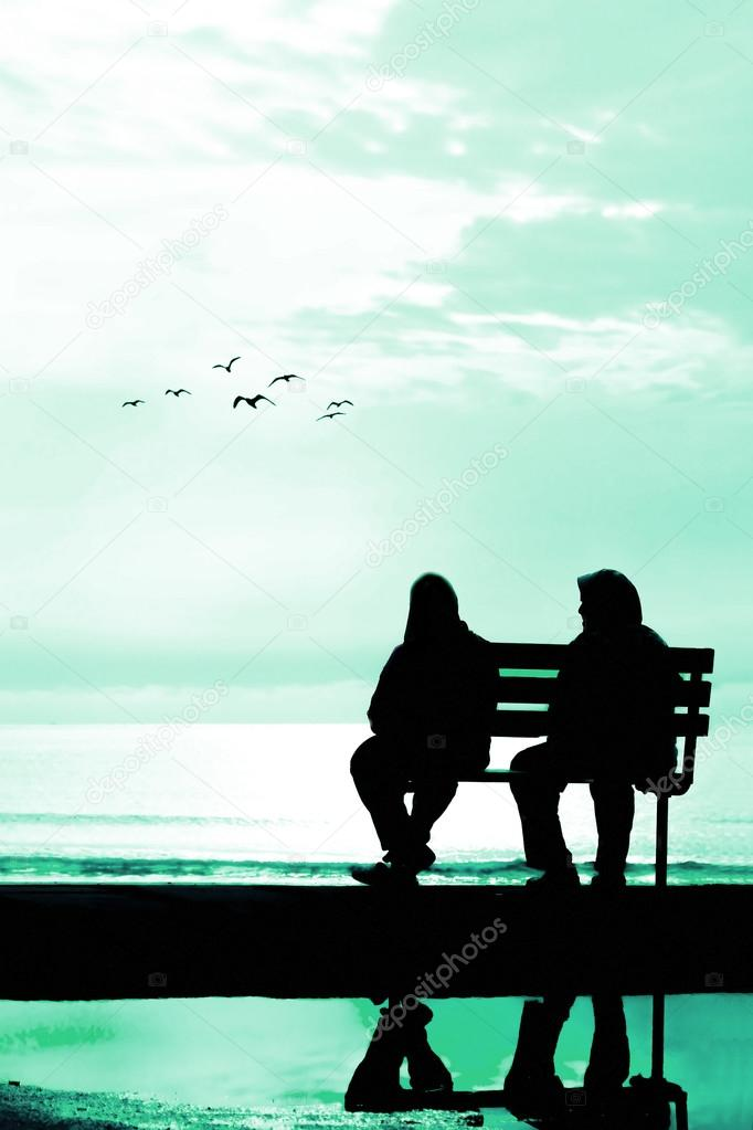 Two friends sitting on wood bench near beach