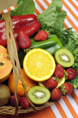 Healthy diet - sources of Vitamin C - oranges, strawberry, bell pepper capsicum, kiwi fruit, paw paw, spinach dark leafy greens and parsley. Vertical.