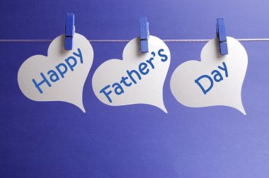 Happy Fathers Day message written on white heart shape tags hanging from blue pegs on a line against a blue background.