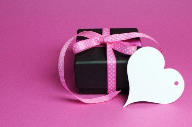 Special small black box present gift with pink polka dot ribbon and white heart shape gift tag with for Mothers Day, birthday, Easter, Christmas, Valentine or special occasion gift