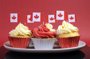 Red and White cupcakes with Canadian maple leaf national flags against a red background for Canada Day or Canadian national holidays.