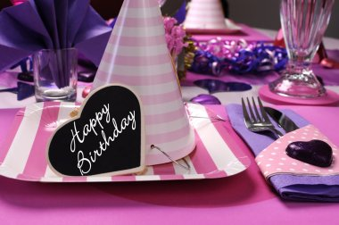 Pink and purple theme party table setting decorations with party hat closeup and Happy Birthday heart message.