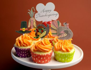 Happy Thanksgiving decorated cupcakes with turkey, pilgrim hat and corn toppers on cake stand against a brown background, with Happy Thanksgiving message.
