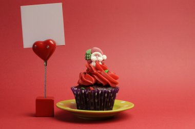 Red Santa Christmas festive cupcake in purple polka dot wrapper on green plate