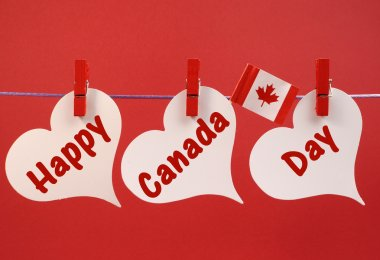 Happy Canada Day message greeting with the Canadian maple leaf flag hanging from pegs on a line