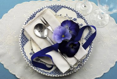 Vintage blue theme table place setting with blue pattern vintage plate, antique silverware and pansy flowers on a blue tablecloth for formal dinning, Christmas, Thanksgiving, birthday or special occasion. stock vector
