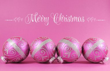 Beautiful fuchsia pink Merry Christmas bauble ornaments with copy space.