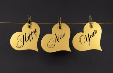 Happy New Year message greeting text on gold hearts hanging from pegs on a line