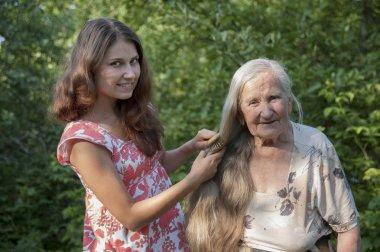 Grandmother granddaughter combs her hair