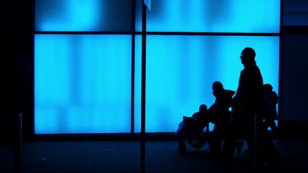 siluety před modré osvětlené skleněné stěně