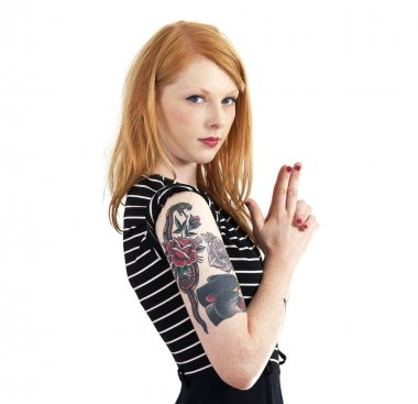 Strawberry Blonde Red Head Leaning Against Wall with Tattoo Arms