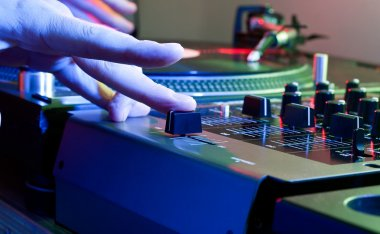 DJs hand tweaks the cross fader of a music mixer