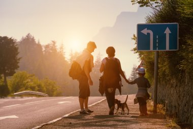 Family backpackers goes on road at sunset