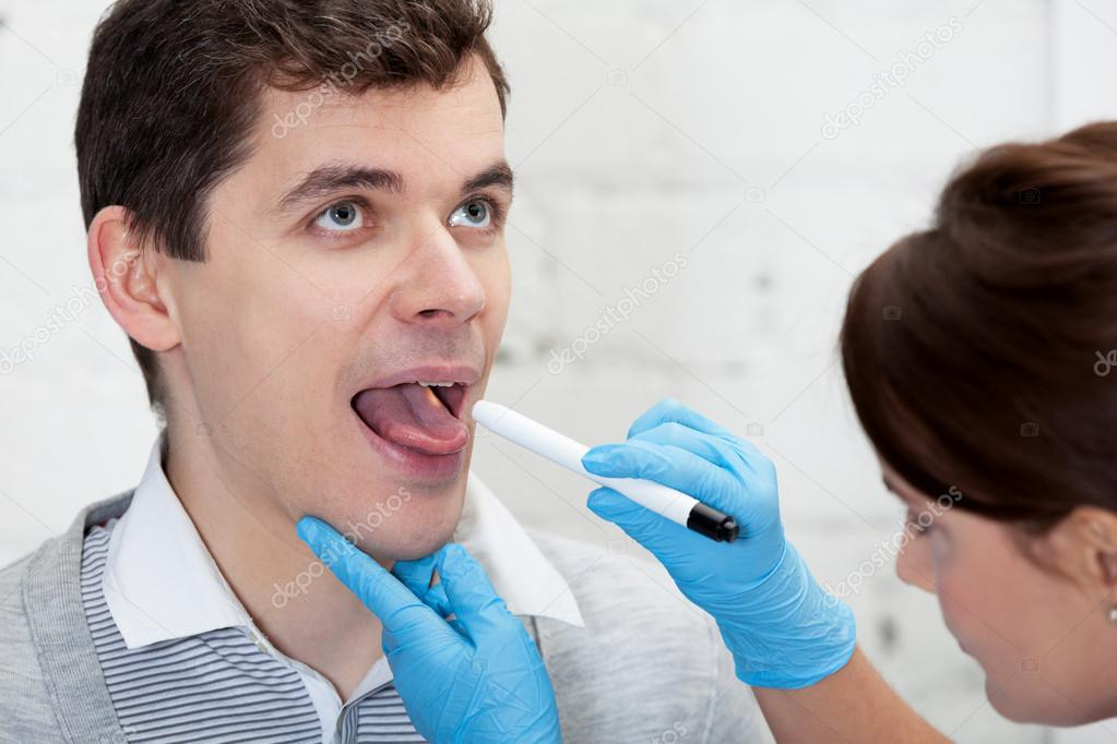 Doctor is checking throat of a patient