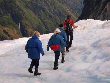 Group of tourists following a guide on a glacier