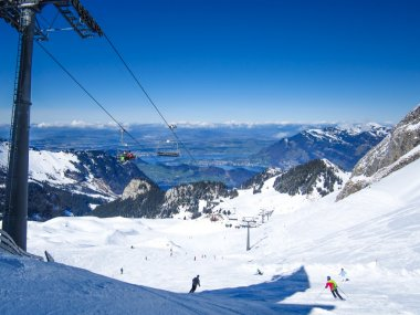 Skiers skiing in Klewenalp ski resort with view to Lucerne lake, Central Switzerland
