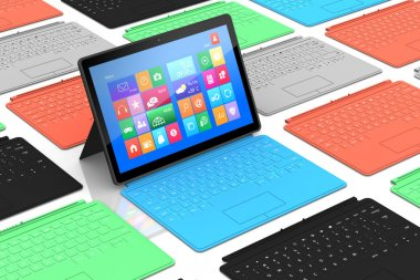 Tablet PC surrounded by colors keyboards.