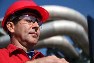 Engineer With Red Hard Hat and Pipelines