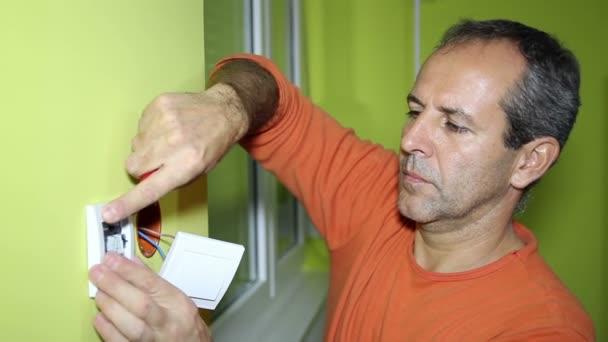 elektrikář instalující elektrický spínač