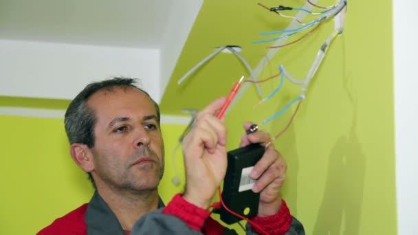 elektrikář s měřicí přístroj a kabely