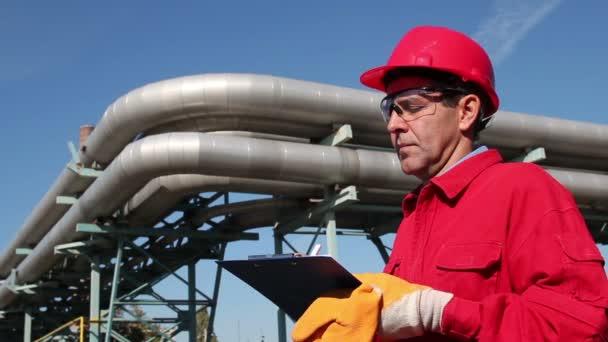 ropné rafinérie dělník v červených montérkách