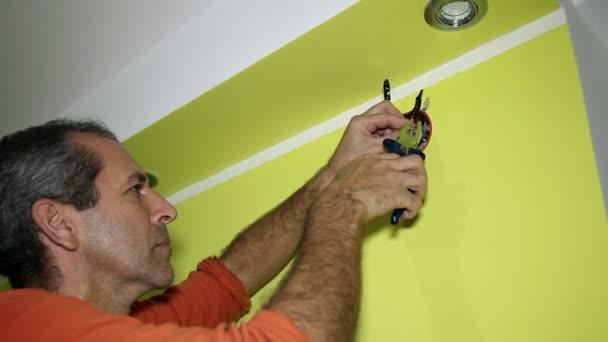 Muž pracující na elektrických instalacích