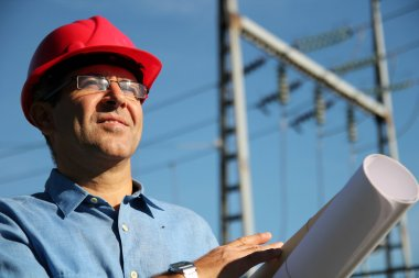 Engineer With Red Hard Hat and Blueprint Under the Power Lines.