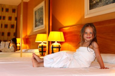 Little girl sitting on a bed