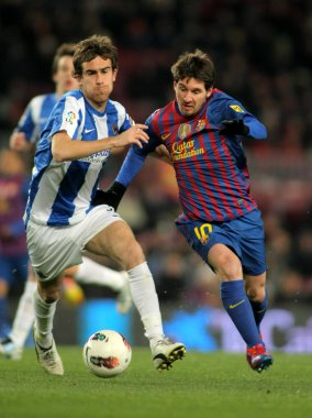 Mikel Gonzalez(L) of Real Sociedad vies with Leo Messi(R) of FC Barcelona