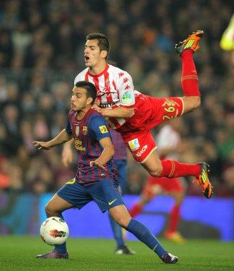 Pedro Rodriguez(L) of FC Barcelona vies with Pedro Orfila(R) of Sporting de Gijon