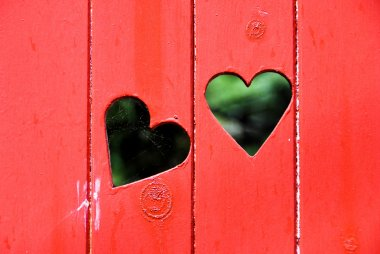 Two heart shapes on a red door