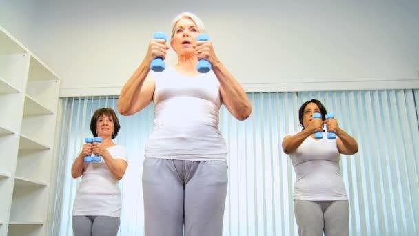 starší samice zvedání závaží jóga skupina